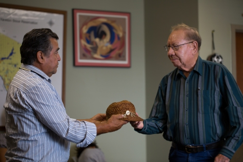 "Lummi Elder Sit-ki-kadem (Doug James) gifts a traditional red cedar hat to Leo O'Conner, Elder and Tribal Treasurer from the Ihanktonwan Oyate (Yankton Sioux). O'Conner was the last person born in the Ihanktonwan village of White Swan that was flooded in 1952 by an Army Corp of Engineers hydroelectric dam project that took place without consent from the Ihanktonwan People. The tribe lost almost 3,000 acres of their homelands when the Fort Randall dam closed. ""On this journey over here I knew this hat was going to be given away, but I didn't know where, and I didn't know who,"" Sit-ki-kadem said. The cedar hat was woven by Tsilixw (Bill James), the Hereditary Chief of the Lummi People, and passed on to Sit-ki-kadem years ago."